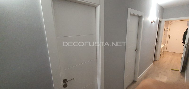 Trabajo de instalación de puertas lacada cuatro ranuras premium y suelo laminado AC5