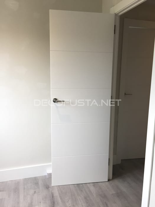 Combinación de puerta lacada con ranuras y suelo laminado gris medio